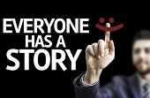 Business man pointing to black board with text: Everyone Has a Story