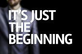 It's Just the Beginning written on a board with a business man on background