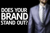 Does your Brand Stand Out? written on a board with a business man on background