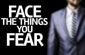 Face the Things you Fear written on a board with a business man on background