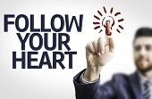 Business man pointing to transparent board with text: Follow your Heart
