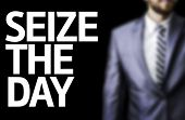 Seize The Day written on a board with a business man on background