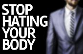 foto of stop hate  - Stop Hating Your Body written on a board with a business man on background - JPG
