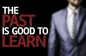 The Past Is Good To Learn written on a board with a business man on background