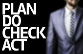 Plan Do Check Act written on a board with a business man on background