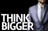Think Bigger written on a board with a business man on background