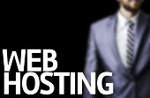 Web Hosting written on a board with a business man on background