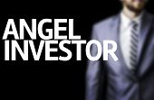 Angel Investor written on a board with a business man on background