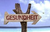 Health (In German) wooden sign with a beach on background
