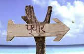 Love (In Hindi) wooden sign with a beach on background