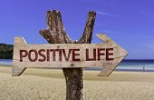 Positive Life wooden sign with a beach on background
