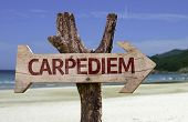 Caperdiem wooden sign with a beach on background