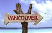 Vancouver wooden sign with a beach on background