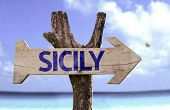 Sicily wooden sign with a beach on background