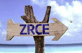 Zrce wooden sign with a beach on background