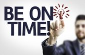 Business man pointing to transparent board with text: Be on Time