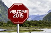 Welcome 2015 written on red road sign with landscape background