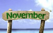 November wooden sign with a beach on background