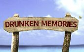 Drunken Memories wooden sign with a beach on background