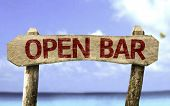 Open Bar wooden sign with a beach on background