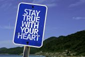 Stay True With Your Heart sign with a beach on background