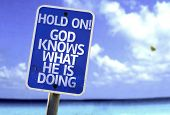 Hold On! God Knows What He is Doing sign with a beach on background