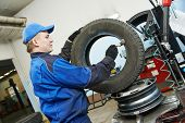Auto repairman lubricating automobile car wheel during tyre fitting or tire replacing