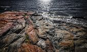 Exposed bedrock and colorful rock formations at rugged Georgian Bay lake shore near Parry Sound, Ontario, Canada.