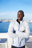 Fit black man with arms crossed standing on sea background