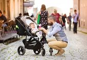 Hipster business man with baby in pram in town