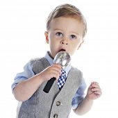 An adorable 2-year old singing (or talking) into a microphone.  On a white background.