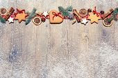 Christmas background with cookies, fir branches and spices on the old grunge wooden board
