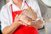 Midsection of male butcher holding fresh meat in shop