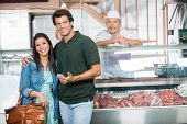 Portrait of loving mature couple smiling in butchery
