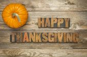 Happy Thanksgiving  - text in vintage letterpress wood type blocks against rustic wood background with a pumpkin