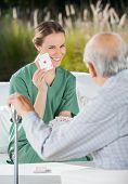 Smiling female caretaker showing ace card to senior man at nursing home