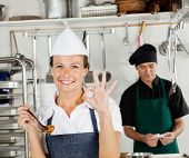 Portrait of happy female chef gesturing okay sign with colleague in background