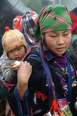 Hmong woman carrying child and wearing traditional attire.