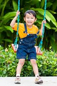asian boy playing swing at playground