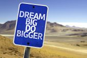Dream Big Do Bigger sign with a desert background