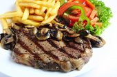 picture of ribeye steak  - A grilled ribeye steak served with mushrooms chips  - JPG