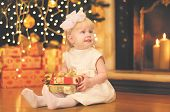 foto of christmas baby  - Christmas magic people concept - happy baby with gift near christmas tree and fireplace
