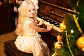 Holiday, Christmas And People Concept - Pretty Little Girl With Piano