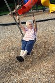 picture of unnatural  - Senior citizen woman on a playground swing - JPG