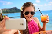 foto of waikiki  - Selfie woman taking self portrait at beach bar during holidays - JPG