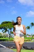 picture of cardio exercise  - Young woman jogging on city street during summer - JPG