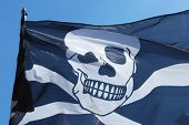 image of pirate flag  - Pirate flag on windy day against blue sky - JPG