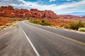 stock photo of curvy  - Curvy road in a dry and desert area with scenic view of orange mesas - JPG
