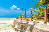 image of beachfront  - tropical beach with palm trees and beach beds - JPG