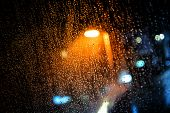 stock photo of rain  - Rain drops on the window with dark streets outside and street lights shining - JPG